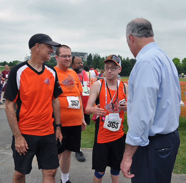 . Photo courtesy of SOPA Wicked Fast coach Scott Otterbein, left, and athletes Tom Gibson and David Miller are greeted by U.S. Senator Bob Casey during the Summer Games at Penn State.