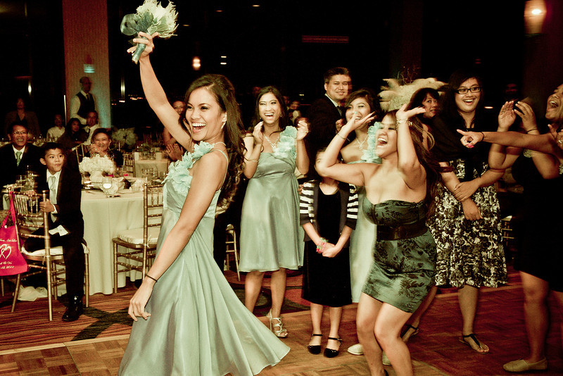 Bridesmaid catching the bouquet toss at wedding reception