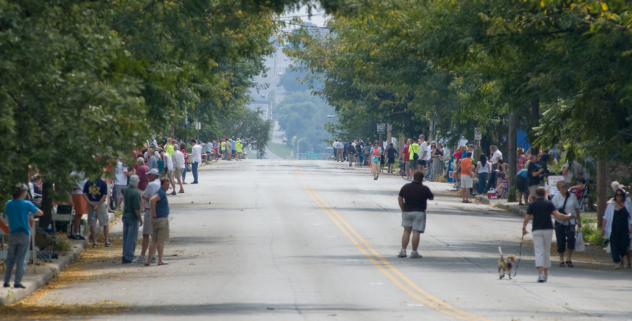 View down Summit. Quite a crowd along the sides of the street. I-35 is visible in the background.