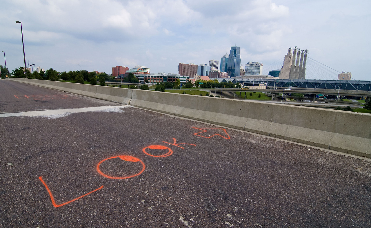 A sign on the road advising riders to enjoy the view from the Summit St. bridge over I-670.