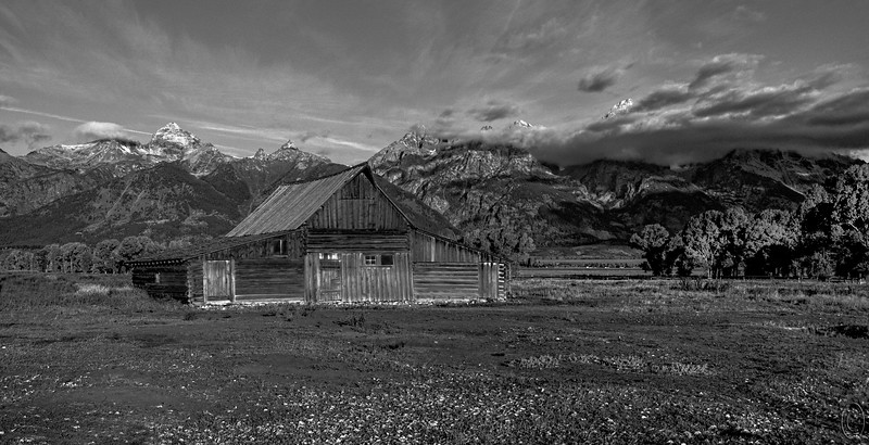 """18 Sep 18We're a bit overdue for a B&W so for B&W Tuesday this week that's what I'll share. IF Ox Bow Bend is the most frequently shot location in Grand Teton National Park, then Mormon Row has to be the second most shot location in the park. Or maybe it's vice versa. Either way it doesn't matter, when you visit that park you will go see both. And if you are a photographer you'll shoot them as well. Oddly, before visiting the park I had no recollection of Mormon Row but being an avid reader of photography magazines I don't know how that happened. Now I see the photos everywhere. Guess it's something like buying a new vehicle and then seeing them everywhere when before you hardly knew of their existence. This was an early morning shot taken just as the clouds broke and the color of the light was quite bluish which doesn't show off the old rustic barns to their best, so I tried to bring back the colors as I remembered them but wasn't able to do it to my satisfaction. That being the case, I thought I might get the effect I desired by switching to B&W and I did. This image views quite differently on my two boxes so I'm uncertain as to how you are going to see it, but hopefully it will look O.K. I've added in a """"bit"""" of grain to give it a 50s film look; some of you may appreciate that, others perhaps not.<br /> <br /> I've adjusted the original as described above plus cropped off a lot of sky that I don't feel added anything worthwhile. And while I didn't do it I probably should have taken out the con trail; I'll leave that as an exercise for those of you who like playing with these mailings.  From Film Days  Nikon D200; 18 - 200; Aperture Priority; ISO 250; 1/1000 sec @ f /7.1."""