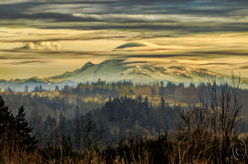 "18 Jan 17	Traveling to Poulsbo yesterday afternoon I noticed that ""our"" mountain was beginning to form some of its own weather, so I kept my eye on it and when I got to a location where I had a reasonably clean view I took a few shots. The temp when we got up was in the low 20s, but it began warming and by this morning it was in the mid 40s, so it isn't surprising that there was some weather developing while we were observing on Monday. The light at the time I snapped the frames was also putting on a beautiful show so the combination made for one of those times when one just had to take a photo. We were even given a tiny amount of atmospheric disturbance in the form of a small low lying cloud bank sometimes referred to as fog in a small section of one of the valleys. I've adjusted this a bit by employing a blending layer to accentuate the differences in the light ""layers"" that you see as you look from foreground to background in the frame. What I was seeing first hand yesterday reminded me greatly of oriental art but it was the real thing. I'm standing on the curb of the road on the edge of the Home Depot parking lot looking south east in the general direction of Dog Fish Bay, now know as Liberty Bay, but I still call it Dog Fish Bay as I think it sounds more authentic.<br /> <br /> The base image was given some micro contrast enhancement, then I applied the Darken blending mode to give it the separation that I saw but the camera couldn't accurately record. Nikon D300s; 18 - 200; Aperture Priority;ISO 200; 1/400 sec @ f / 8."