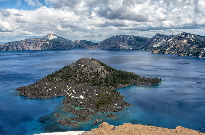 21 Aug 19Since we've made but the one visit to Crater Lake what I write today is mostly conjecture. You are looking at Wizard Island and directly in front at 6 o'clock is Fumarole Bay and at 3 o'clock is Governors Bay. The island is located near the western edge of the crater. While we were there we watched a couple of power boats and a single sail boat cruising around the lake. You can see one boat dock/float in Governors Bay and from a different angle you can see what looks to be a boat shelter there also but on the island itself. There is also a small craft heading into Governors Bay. At one point there was a small power craft in Fumorale Bay and folks walking on what looks to be a small island in front of the green water from which I thinking the bay got its name.  At the north end of the crater there is a tour boat service and likely a boat launch but I can't tell from the little brochure you get when you enter the park. The white you see at the bottom is snow and I had to walk over a large section to get to the rocky area where I took the shot. One could get a bit closer but the nerves wouldn't let me so the result is the rocky soil and snow in the foreground. Need to go back and really check out this beautiful national park.<br /> <br /> Other than some straightening and a bit of contrast enhancement this is what the camera saw. Fumarole Bay   Nikon D500; 18 - 200; Aperture Priority; ISO 200; 1/400 sec @ f /11.