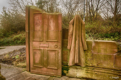 Carved in red sandstone by Colin Wilbourn and Karl Fisher on location in 1985. It represents the ground floor of a house complete with door, fireplace, furniture and a carpet. A coat hangs by the door and books lie open on the table.