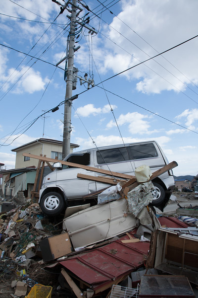 As if as piled up on purpose on this electricity pole bulding debris  with a car on top.