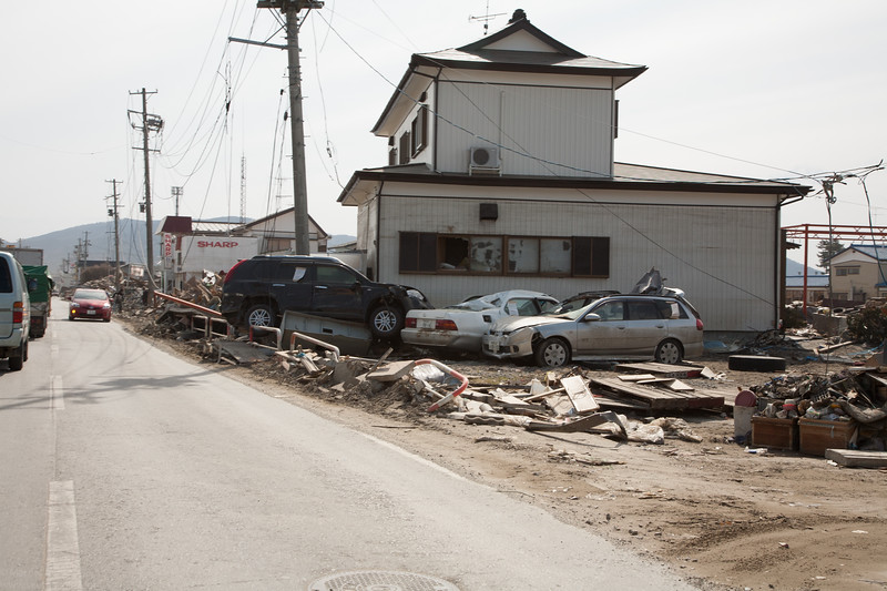 Wrecked cars piled against a house.
