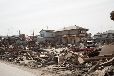 An incomprehensible  chaos of wood, twisted metal, fallen utiliy poles, a fishing net and a smashed car. In the midlle a house perilously standing on some remaining beams.