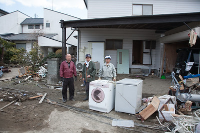 In some houses the clueing up had begun and I was that my hands could be of some use. These three men were cleaning up a house. All the appliances are damaged beyond repair as is the the car on the right . The heavy soaked tatami mats were very heavy to carry out.