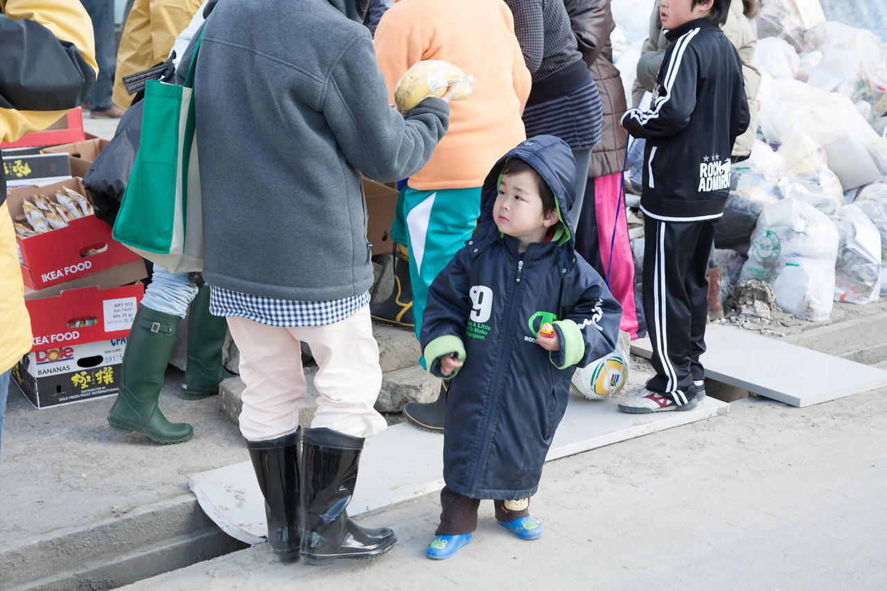 A young boy clutching his lollipop.