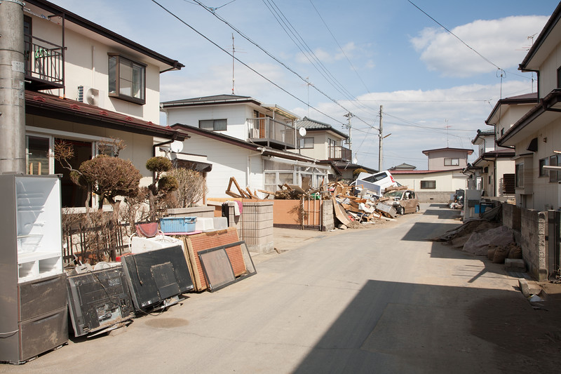 Some houses have been cleared already. Damaged applieances and soaked tatami mats are orderly piled up outside.