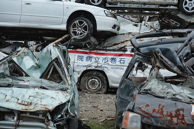 Everywhere piled up caracasses of destroyed vehicles. Amongst them an ambulance car of the Inshinomaki Municipal Hospital.