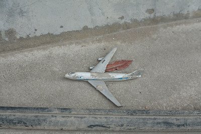 A model plane, mermory of an air travel stranded on a concrete slab.