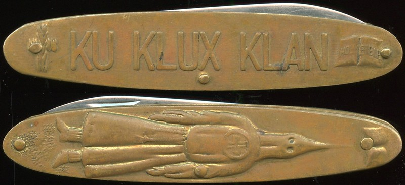 KU KLUX KLAN<br /> Lot 484:  Pocket knife, gilt br, stainless steel blade:  (emblem) KU KLUX KLAN (Holy Bible) // (standing hooded and robed knight); incuse on blade: TAYLOR / CUTLERY // Surgical / Japan.  With blade folded 84x17mm.   G3-(EV$32-$64)-MB$20 - SOLD $55