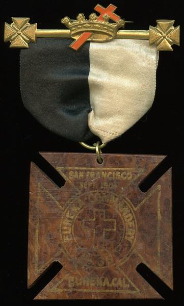 SAN FRANCISCO -- Knights Templar<br /> <br /> Lot  381  Hanger:  KT emblem // (pin); ribbon: black/white; badge: SAN FRANCISCO / SEPT. 1904 / EUREKA COMMANDERY / (cross) / 1835 / EUREKA, CAL. // (uniface), gilt imprint on wood, Maltese cross 63mm; overall 77x129mm.  Highly unusual!     G4-($16-$32) Sold as part of group lot 405 $555.00