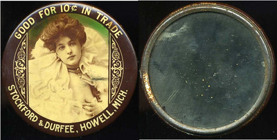 M069  GOOD FOR 10¢ IN TRADE / (Evelyn Nesbitt facing – Dunn type 12) / STOCKFORD & DURFEE, HOWELL, MICH. // edge imprinted: CRUVER MFG. CO., CHICAGO, multicolored celluloid rd 56mm.  Mirror: scattered small black specks; celluloid: very light rubbing.   G4-EV9