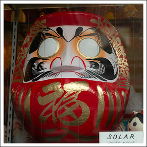 A Daruma in a shop window.  He was a priest who spent so long meditating that his legs melted away.  If you paint one eye black and wait long enough your wish will come true.  Then you can paint the other eye black.