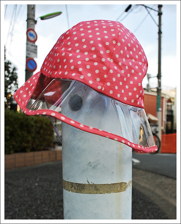 This child's rain hat adorned the corner street post.  I wonder if the owner found it.