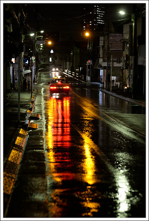 The bus street around the corner, on a rainy night.