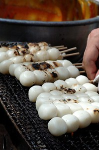 Toasted rice balls.  After toasting they are coated with the sweet soy sauce based sauce you see in the background.