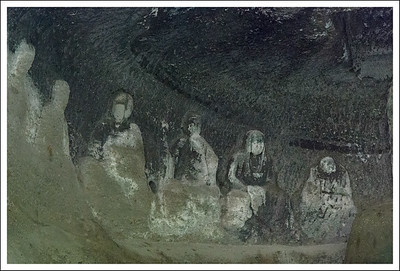 Figures carved into the back wall of a shallow cave.