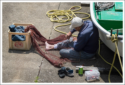 Another fisherman mending his nets.