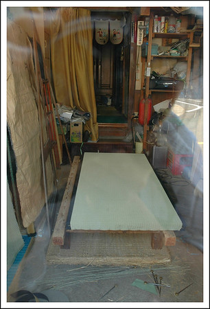 Our neiborhood Tatami shop, taken through the glass of his front door.  He is the one we call to replace our tatami.