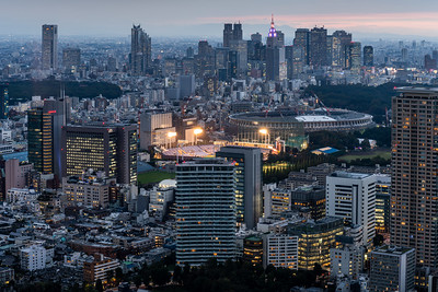 View of Meiji Jingu Stadium and Shinjuku skyscrapers at dusk.