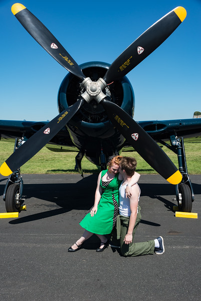 Happy 1940's couple enjoy a romatic moment in front of a Grumman F8F Bearcar