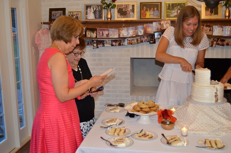 Kathy and Marybeth look at cards while Anne serves up the cake