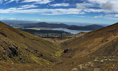 The long way down the other side of the Tongariro Alpine Crossing with views of Lake Rotoaira in thre middle ground  and views of Lake Taupo in the distance