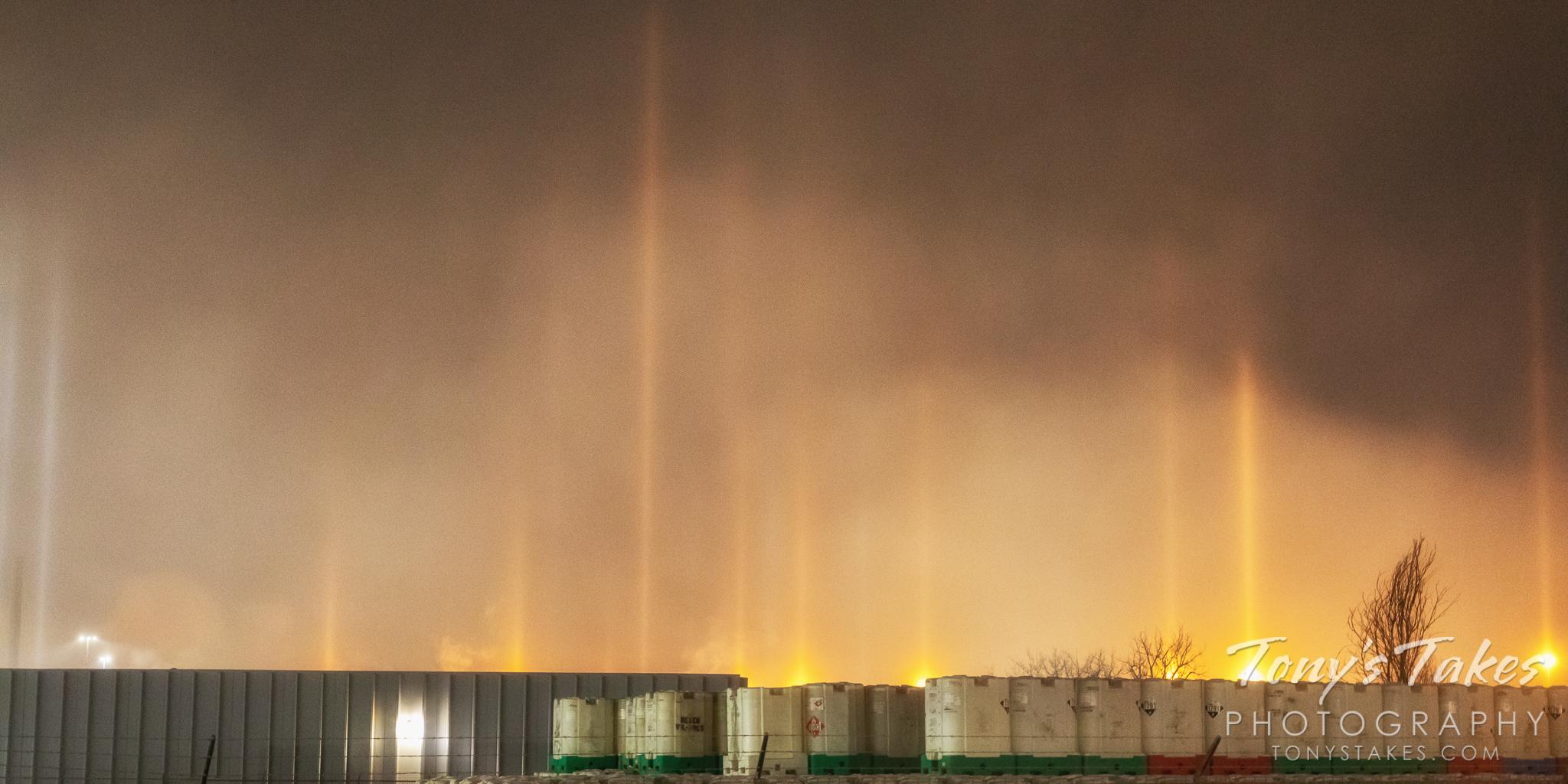 Light pillars rise above a railyard in Denver, Colorado. (© Tony's Takes)