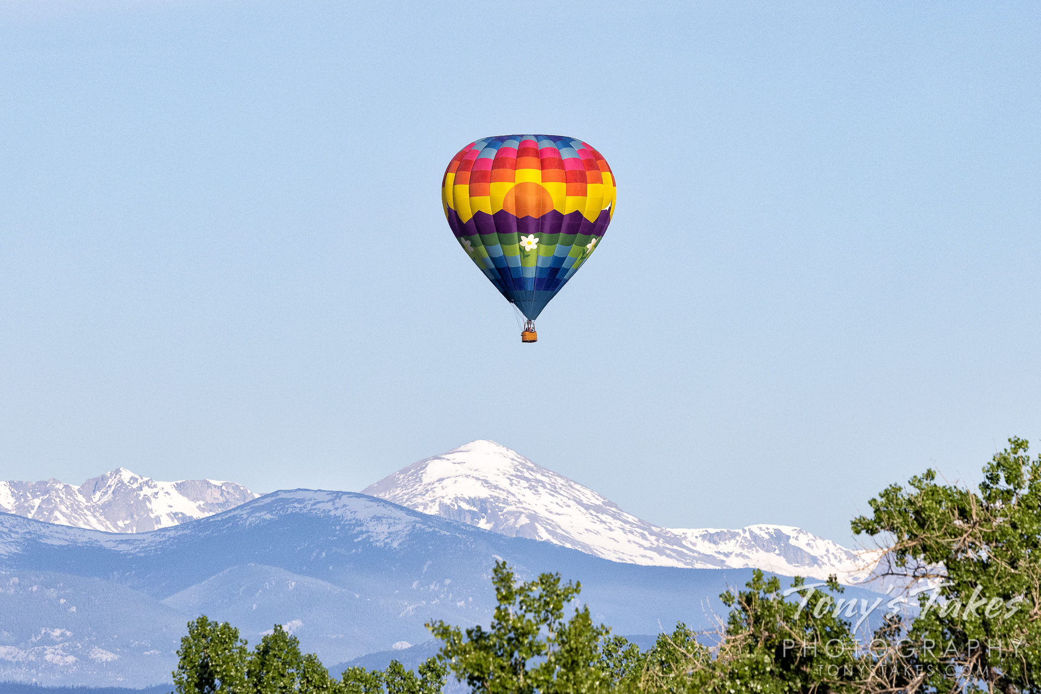 A hot air balloon on the Colorado Front Range with the Rocky Mountains in the background. (© Tony's Takes)