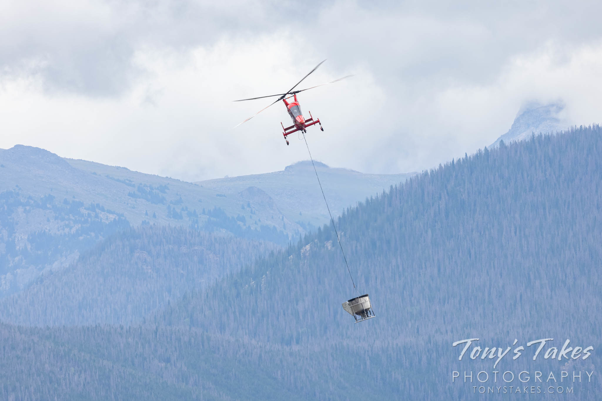 A helicopter drops seeds on the burn area of the East Troublesome Fire. (© Tony's Takes)