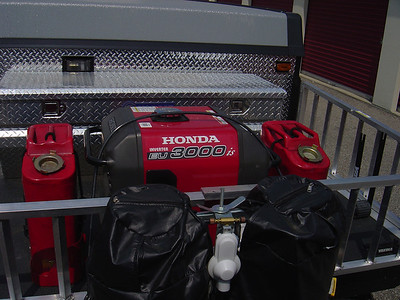 EU 3000is generator with two Gerry gas cans.  Output 3000 watts 23.3 AMPS 120 Volts and 12 AMPs 12 volts.