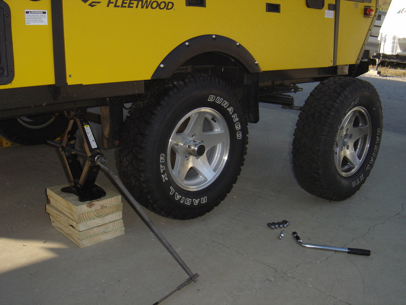 Jack, and maybe wood blocks to raised the PUP in order to change a tire.  Also make sure that the lug wrench is capable or removing both the mounted tire as well as the spare.