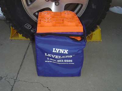 Lynx blocks for leveling.  Alternatively you can use wooden boards. Note - the Lynx blocks can be placed under the tongue jack or stabilizer jack when you have parked on sand or wet soil.