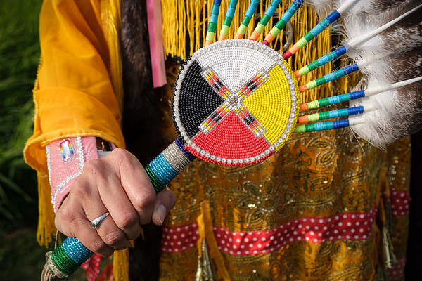 The simplicity and color of this image are what make it one of my favorites. The Indigenous medicine wheel, the four colors, all the beadwork, and the power in her hand as she holds it. To me, it says DIGNITY and pride in her culture.