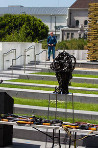 An LAPD officer guards seized guns. One of Mr. Zayas' sculptures made from guns in the foreground.