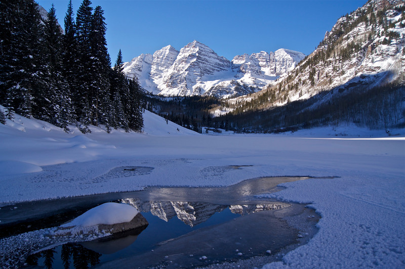 A small clear pool in the frozen surface of Maroon Lake reflects the winter Bells; Colorado Elk Range.