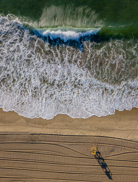 An Aerial View Of Lifeguard Stand Shadows and Tractor Lines In The Sand and Gorgeous Green Ocean Waves 7/2/20