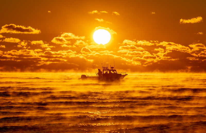 A Boat Passing In Front of Rising Sun With Sea Smoke On Ocean 11/23/18