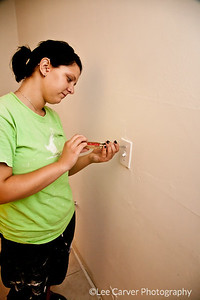 Young women perform numerous construction tasks.