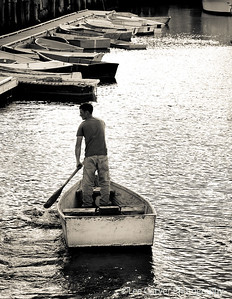 Man pilots skiff with one oar