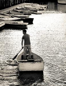 Man pilots skiff with one oar