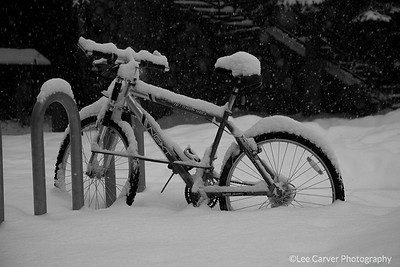 Bicycle contrasts with heavy snowfall.