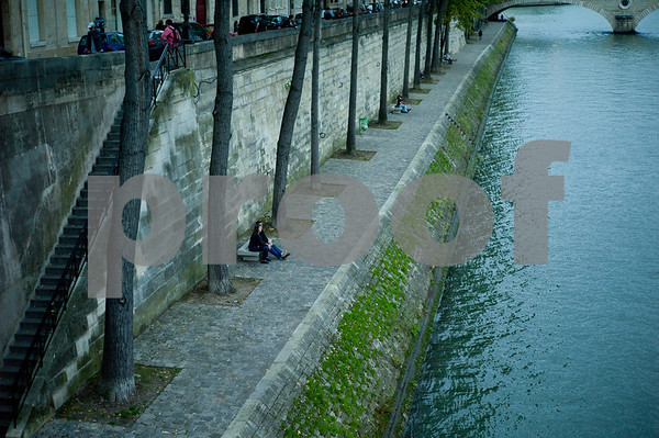 Early evening strollers take a rest beside the Seine.