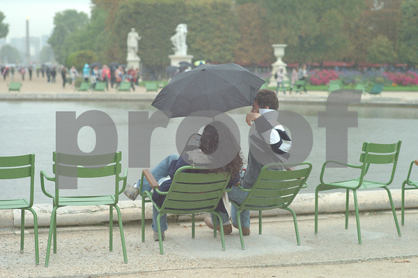 Umbrellas come out to cheer a rainy day in Paris. Couples ignore the rain for a romatic memory.  People continue on Jardin Des Tuileries and Espace Pierre Jardin.