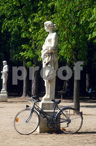 Bicycle loves are Bicycle parked in Luxemburg Gardens next to stoic staturaruy.