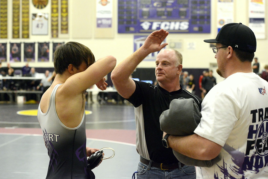 . Mountain View coach Scott Barker goes to give wrestler Jackson Gilbert a high-five after Gilbert pinned Thompson Valley\'s Hunter Williams in 18 seconds to win the 160-pound title at the Torgerson Invitational at Fort Collins High School on Saturday.