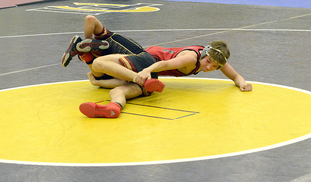 . Cody Thompson of Loveland tries to hook the ankle of Windsor\'s Jacob Parker in their 106-pound final at the Torgerson Invitational at Fort Collins High School on Saturday. Thompson dropped a 7-1 decision.